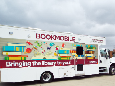 photo of colorful new bookmobile with red, blue yellow green and orange graphics
